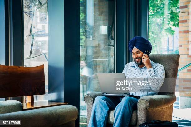 Man wearing turban using laptop and cell phone in armchair