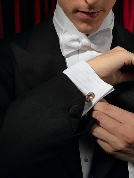 Man wearing tuxedo, adjusting cufflink, mid section, close-up