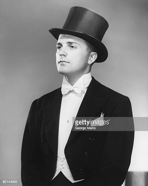man wearing tuxedo and top hat posing in studio, (b&w) - top hat stock pictures, royalty-free photos & images