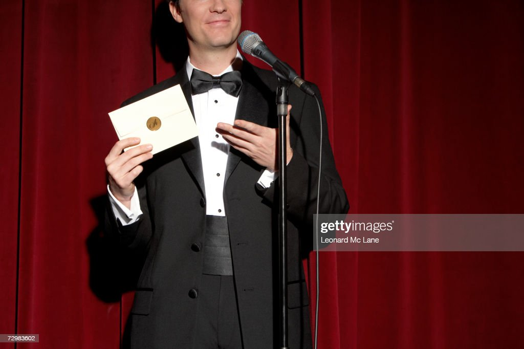 Man wearing tuxedo standing on stage, showing envelope, mid section : Stock Photo