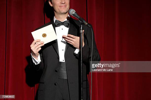 man wearing tuxedo standing on stage, showing envelope, mid section - award stock pictures, royalty-free photos & images