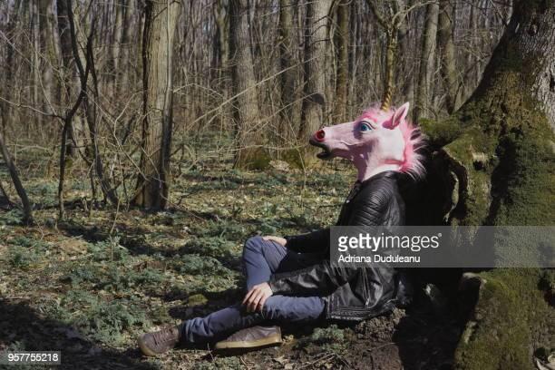 Man Wearing Unicorn Mask While Sitting On Field
