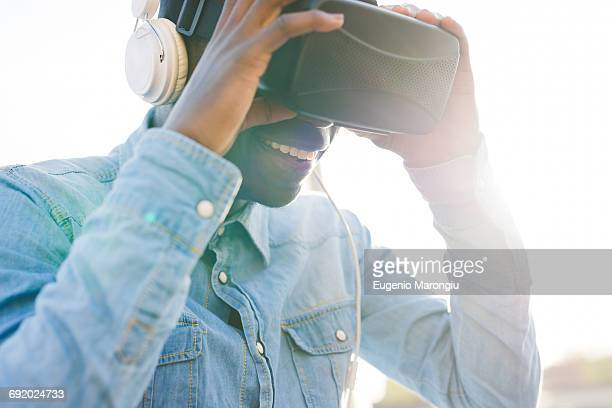 Man wearing virtual reality and headphones smiling