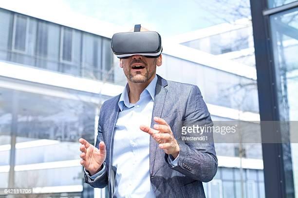 Man wearing virtual reality glasses outdoors