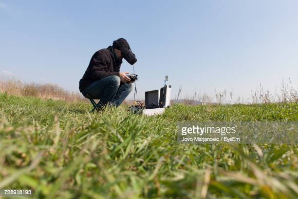 Man Wearing Virtual Reality Headset Using Remote Control On Grassy Field Against Clear Sky