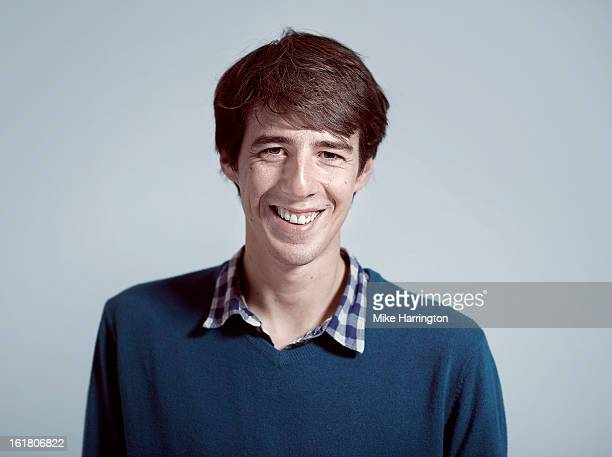 Man wearing V-neck jumper smiling direct to camera