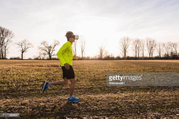 Man wearing VR glasses running in rural landscape