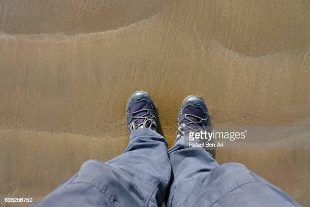 man wearing walking shoes standing on sand - rafael ben ari stock-fotos und bilder