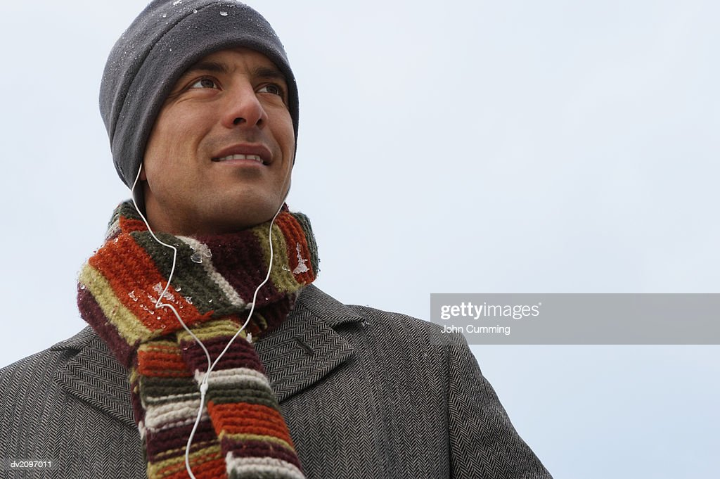 Man Wearing Warm Clothing and Listening to His MP3 Player : Stock Photo