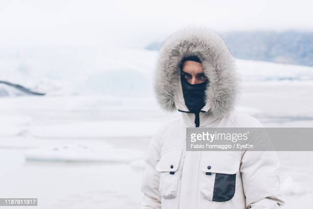 man wearing warm clothing during winter - hood clothing stock pictures, royalty-free photos & images