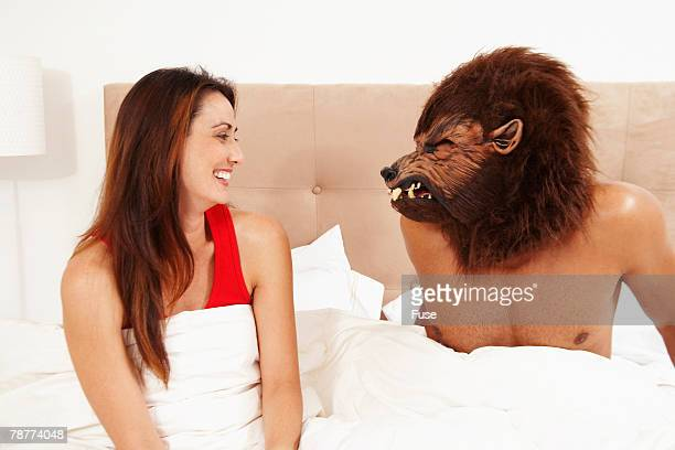man wearing werewolf mask to bed - werewolf stock photos and pictures