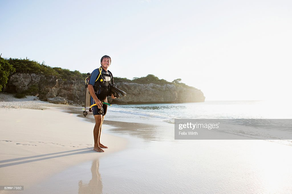 Man wearing wetsuit standing on beach : ストックフォト