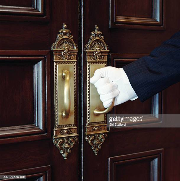 Man wearing white gloves, opening door, close-up