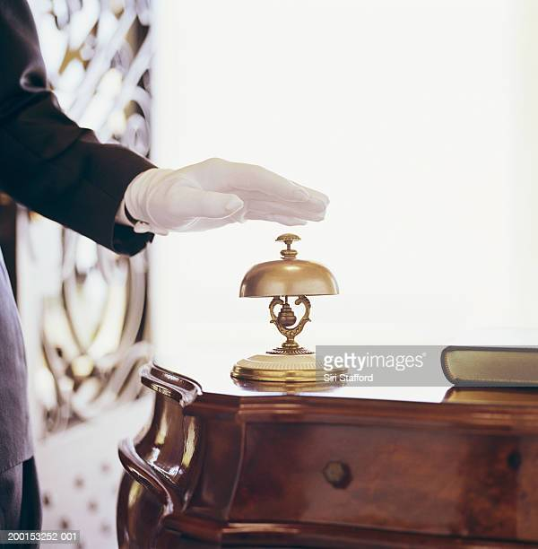 man wearing white gloves, ringing desk top bell (mid section) - social grace stock pictures, royalty-free photos & images