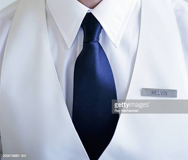 man wearing white shirt and blue tie with name tag - camisa blanca fotografías e imágenes de stock