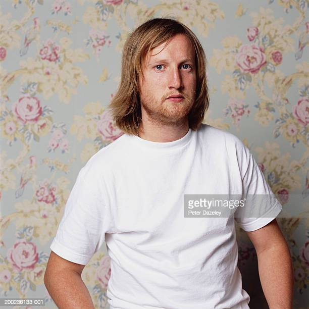 man wearing white t-shirt standing by floral-papered wall, portrait - white t shirt stock pictures, royalty-free photos & images