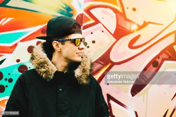 man wearing winter coat at graffiti wall - フード付きコート ストックフォトと画像
