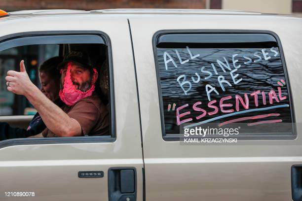 A man wearing women's underwear as face mask gives a thumbs up as he protests against the coronavirus shutdown in front of State Capitol in Madison...