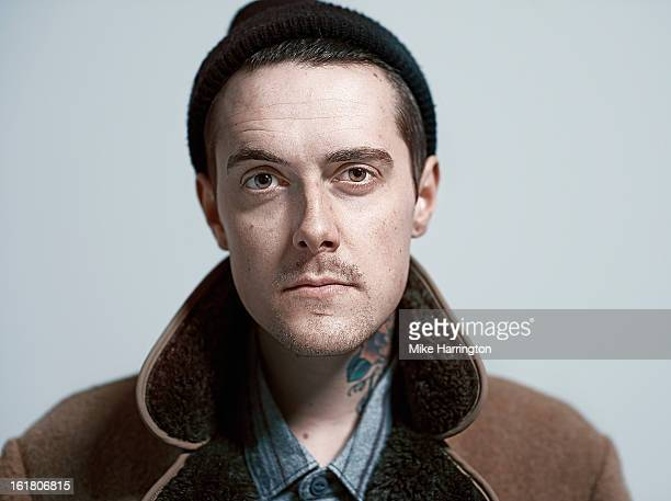 Man wearing woolly hat and coat looking to camera.