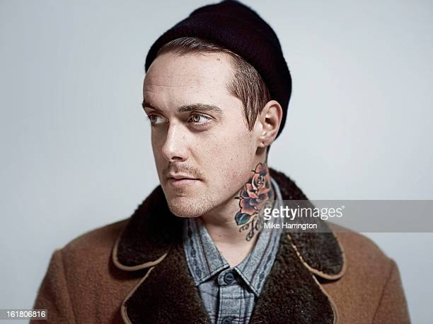 Man wearing woolly hat and coat looking to side.
