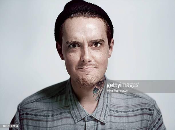 Man wearing woolly hat pulling humorous face.