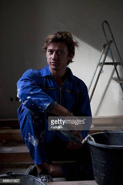 Man wearing workwear sitting with paint bucket, portrait
