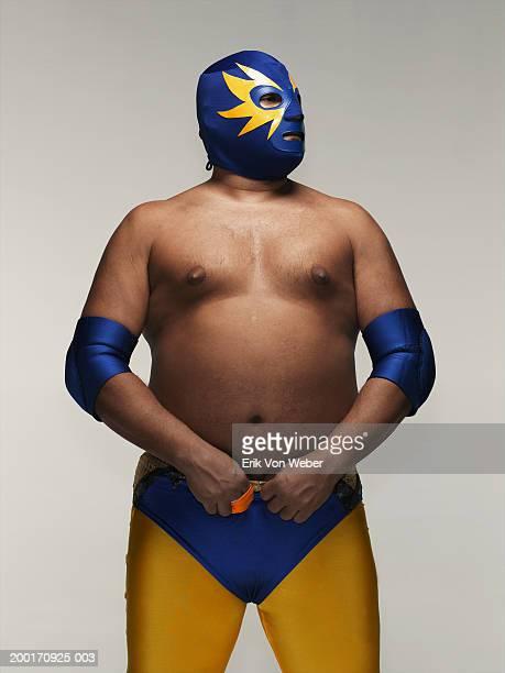 Man wearing wrestler costume and mask, looking away