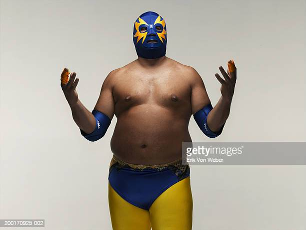 Man wearing wrestler costume, holding hands up