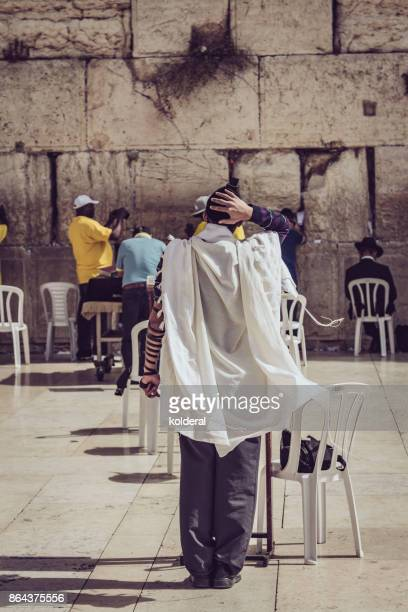 Man wearing yarmulke and tefillin praying next to Western Wall of the Temple in Jerusalem