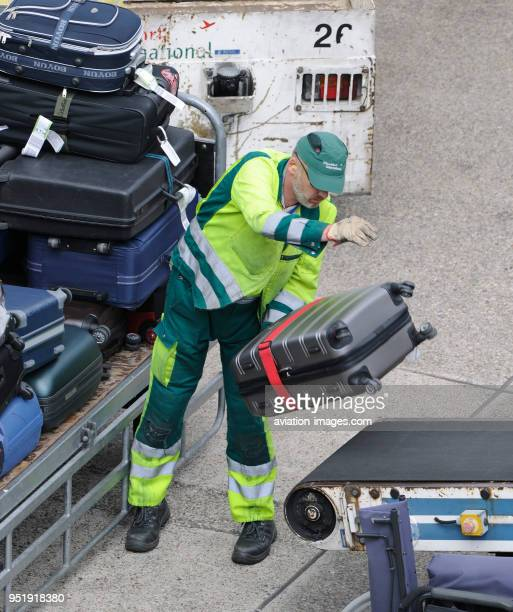Man wearing yellow highviz jacket loading bags from a trolley onto a baggagebelt truck