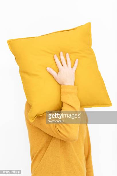 man wearing yellow pullover hiding face behind yellow cushion - cojín fotografías e imágenes de stock