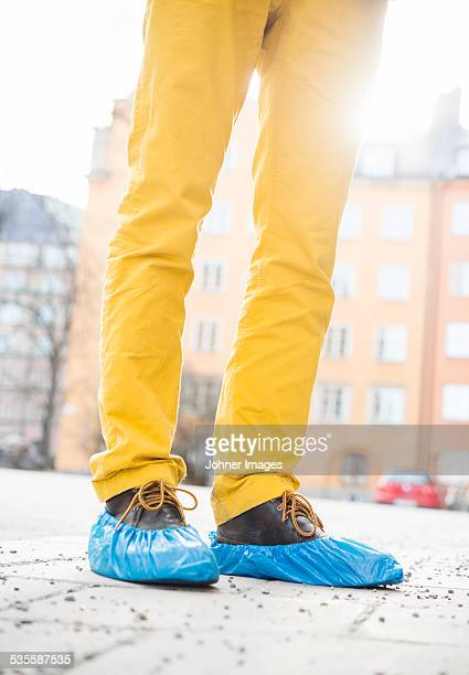 man wearing yellow trousers and shoe protectors, low section - shoe covers stock pictures, royalty-free photos & images