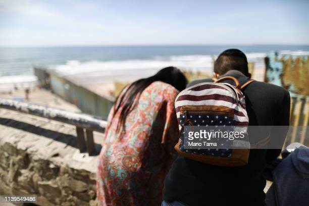 A man wears a backpack decorated as an American flag above the border barrier at the USMexico barrier on the beach on March 31 2019 in Tijuana Mexico...