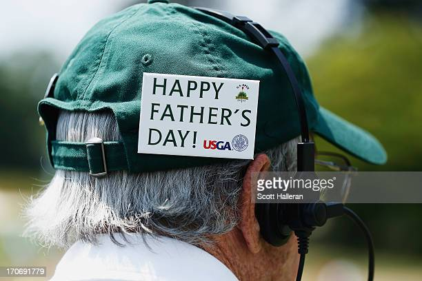 A man wears a badge on his hat that says 'Happy Father's Day' during the final round of the 113th US Open at Merion Golf Club on June 16 2013 in...