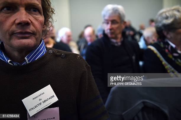 A man wears a badge with an inscription which translates as Dental Association collective as he waits with other victims the start of the trial of...