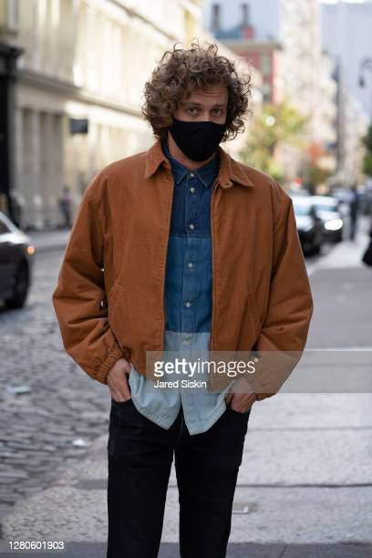 Man wears a black face mask, orange corduroy jacket, multi colored blue chambray denim shirt with black denim pants in Soho on October 15, 2020 in...