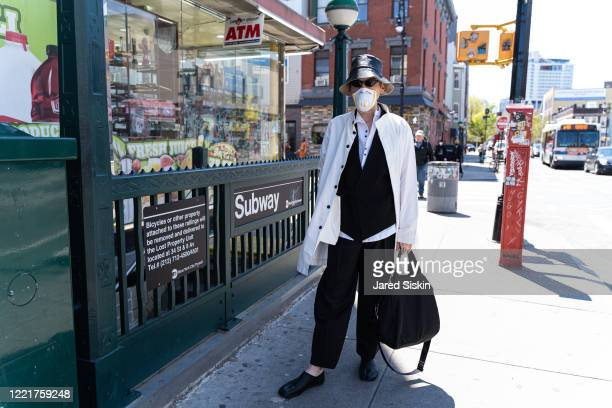 Man wears a black leather bucket hat black Prada tote bag white spring coat black vest and a white long sleeve shirt paired with black pleated pants...