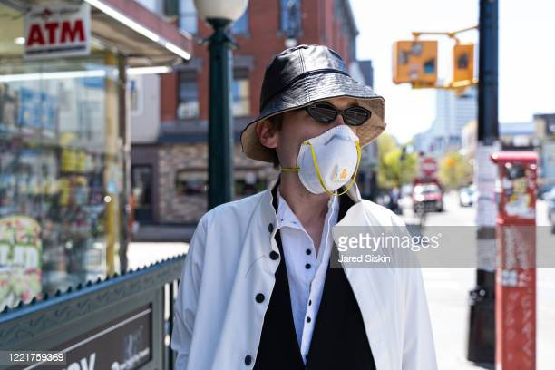 Man wears a black leather bucket hat black white spring coat black vest and a white long sleeve shirt on April 28 2020 in Williamsburg Brooklyn New...