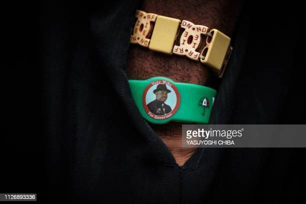 A man wears a bracelet of Rivers state's Governor Ezenwo Nyesom Wike at a polling station for Presidential and General election in Port Harcourt...