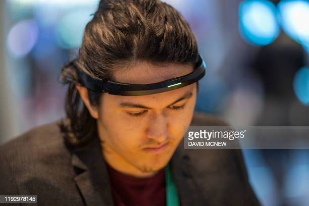 Man wears a Brainco Focus 1 wearable that detects brain activity while playing concentration challenge games are displayed at the 2020 Consumer...