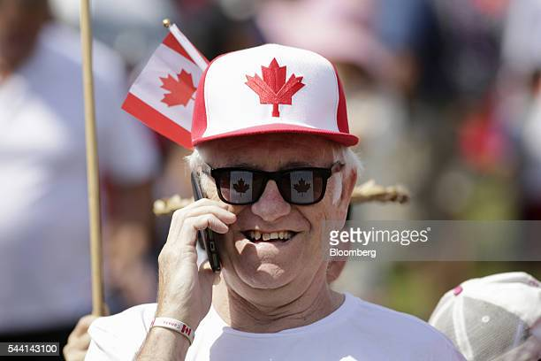A man wears a Canadian flag themed hat while talking on mobile phone during Canada Day celebrations on Parliament Hill to begin in Ottawa Ontario...
