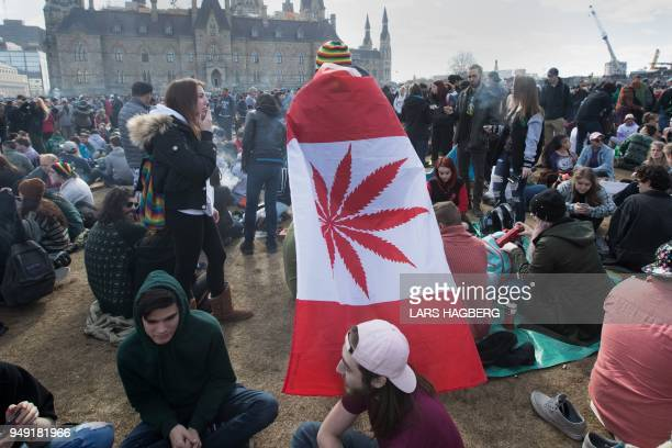 A man wears a Canadian maple leaf flag with marijuana leaf during the annual 4/20 rally on Parliament Hill in Ottawa Ontario Canada on April 20 2018