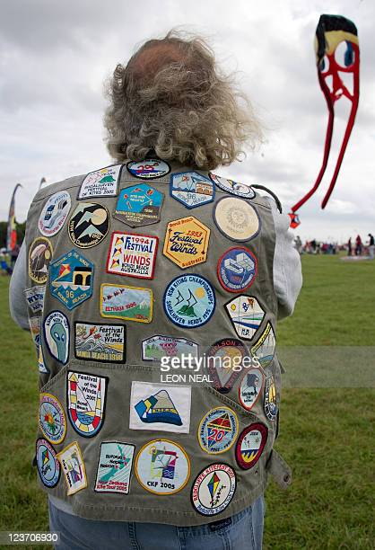 A man wears a coat adorned with many kite festival badges from around the world as he flies a kite at the 25th annual Bristol International Kite...