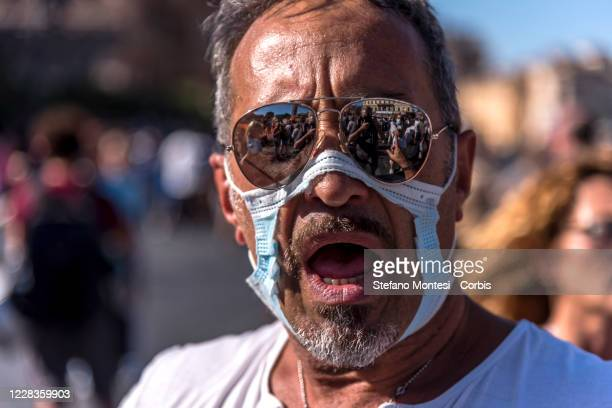 "Man wears a cut out face mask during the protest from ""No Mask"" movements on September 5, 2020 in Rome, Italy. A demonstration organized by ""No..."