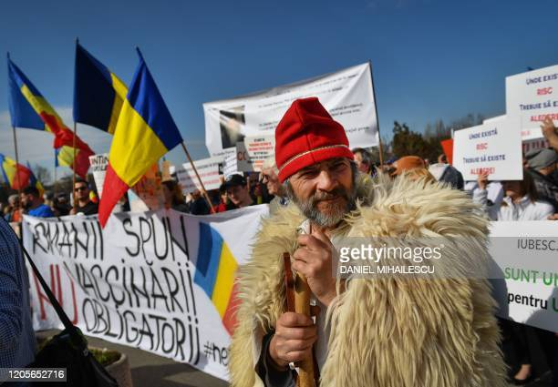 A man wears a dacianinspired outfit next to a banner reading Romanians say NO to the mandatory vaccination during a demonstration against a draft law...