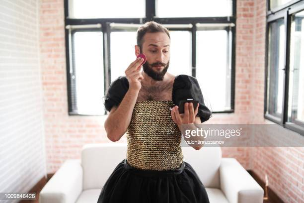 man wears a dress and applying make-up - men wearing dresses stock photos and pictures