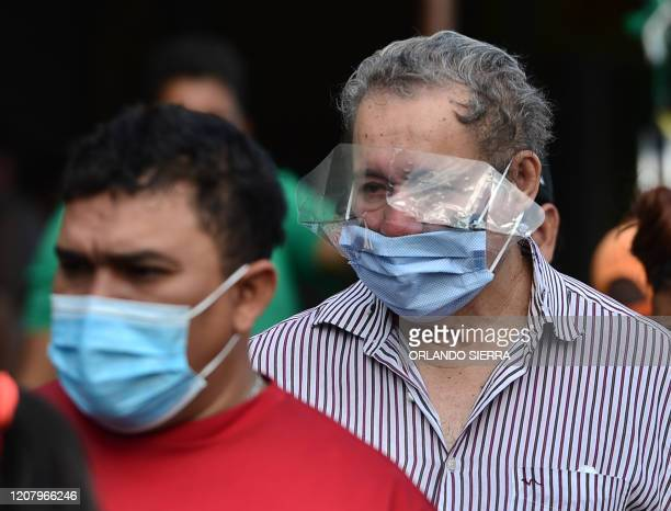 A man wears a face mask and covers his eyes against the spread of the new coronavirus at a street market in Tegucigalpa on March 22 2020 Authorities...