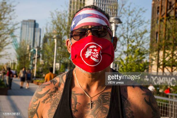 A man wears a face mask and the Puerto Rican flag on his head visit Domino Park on May 15 2020 in Brooklyn NY COVID19 has spread to most countries in...
