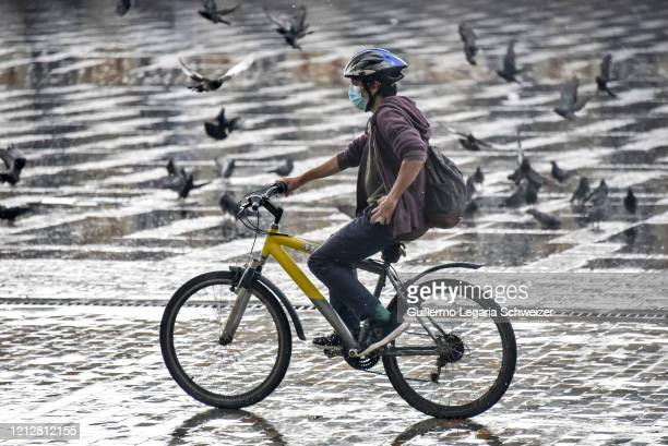 Man wears a face mask as a preventive measure against the spread of the COVID-19 as he rides his bicycle at the historic downtown on March 16, 2020...