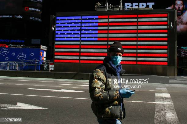 A man wears a face mask as he check his phone in Times Square on March 22 2020 in New York City Coronavirus deaths soared across the United States...